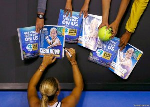 Dominika Cibulkova of Slovakia signs autographs after defeating Victoria Azarenka of Belarus in their women's singles fourth round match at the Australian Open tennis tournament in Melbourne.